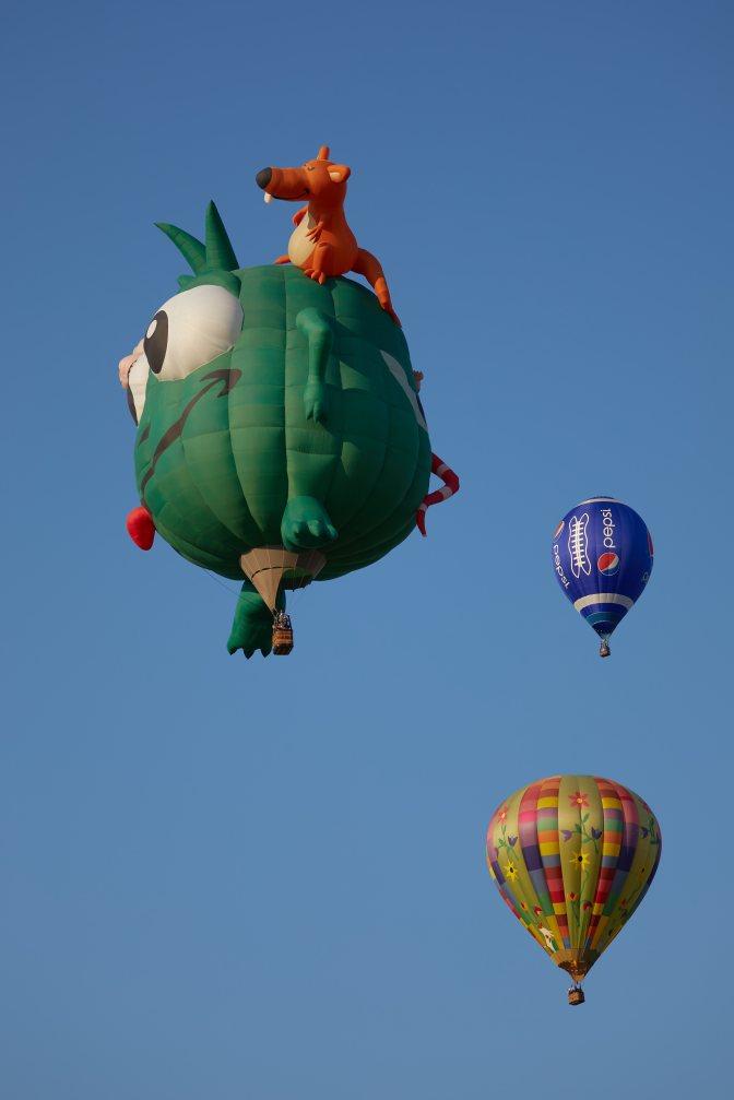 Green monster balloon, blue ballon, and multicolored balloon in sky.