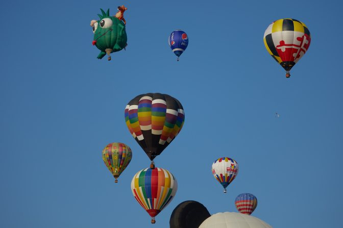 Mass ascension of several multicolored balloons, with green monster balloon in background.