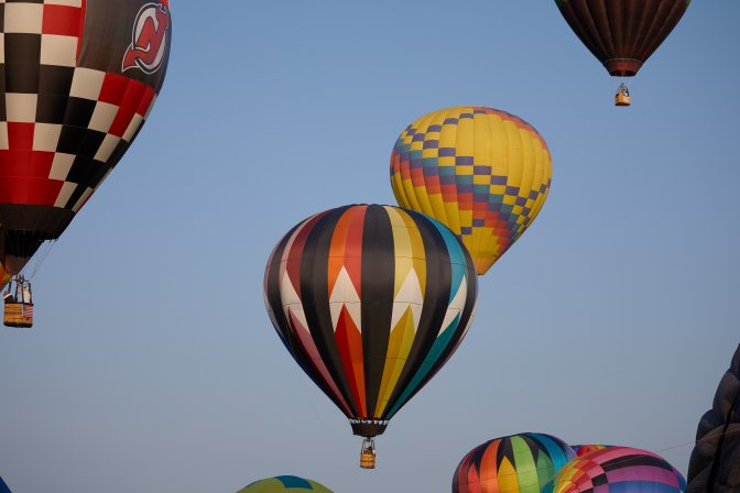 Several multicolored balloons rising into the sky.