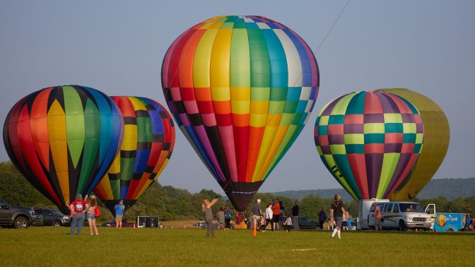 Four multicolored balloons on ground, awaiting takeoff.