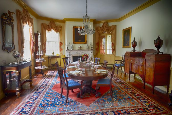 Dining room, with table with six chairs in center of room, chandelier hanging from ceiling, and fireplace along far wall.