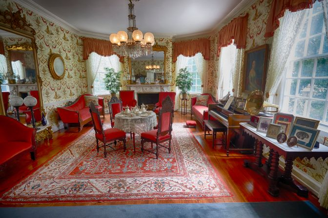 Formal parlor, with table set for tea, piano, and sofas.