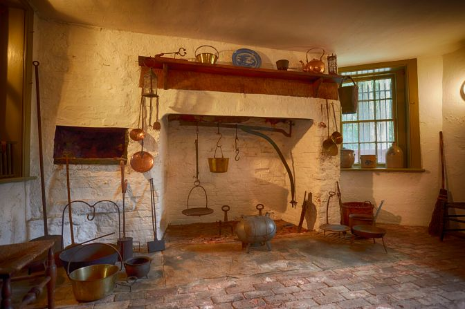 Kitchen with open hearth, surrounded by cooking implements.