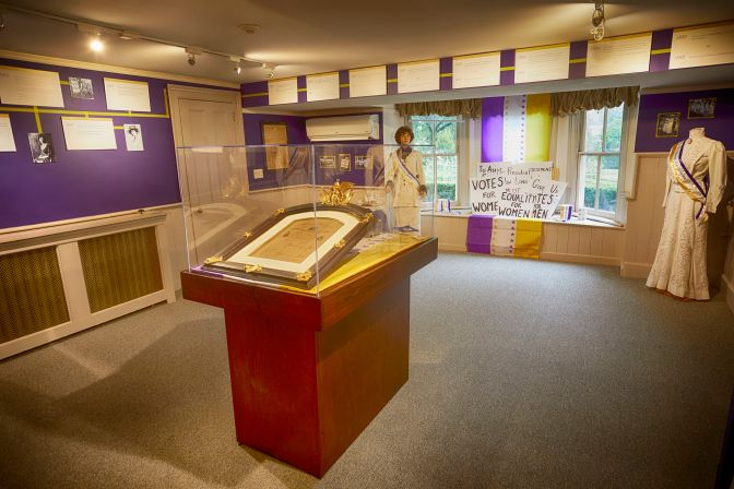 Room-sized display on Suffrage movement, including informational placards and women's suffragette dresses.