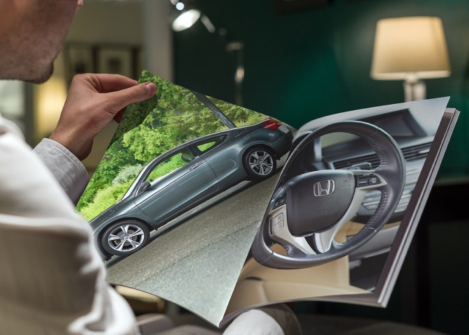 Image of man holding brochure, with photos of 2012 Honda Accord in brochure.