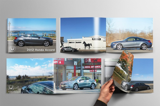 Brochures with photos of 2012 Honda Accord on table, with hand of person flipping through one of the brochures.