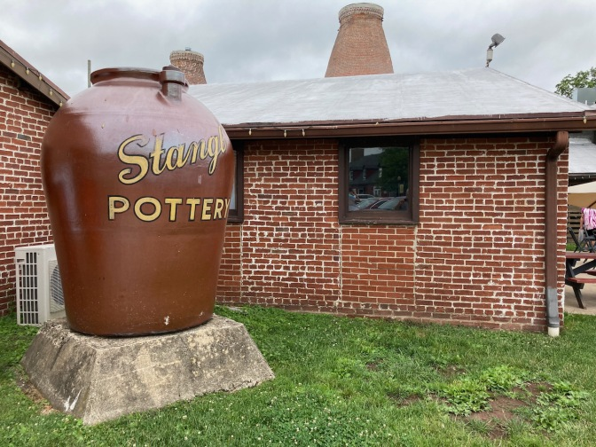 Large pot that says STANGL FACTORY on outside, beside brick building.