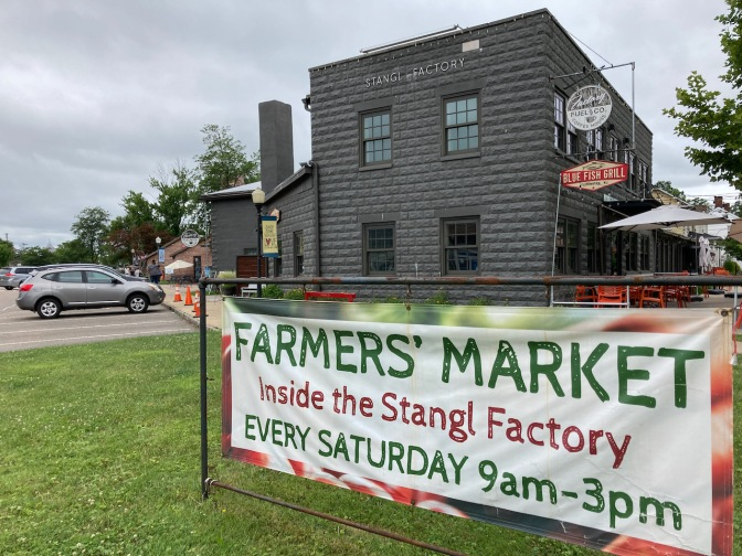 Exterior of Stangl Factory, with sign on lawn that says Farmers' Market - Inside the Stangl Factory Every Saturday 9am - 3pm.