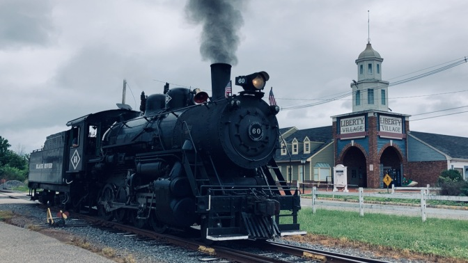 Steam locomotive on tracks approaching station.