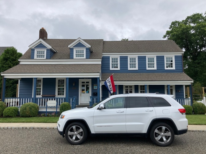 White Jeep Grand Cherokee parked in front of the Blue House.