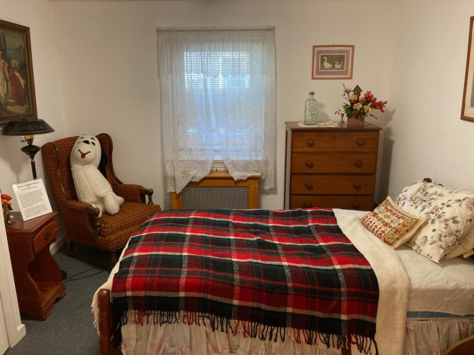 Small room, with bed, dresser, and chair.