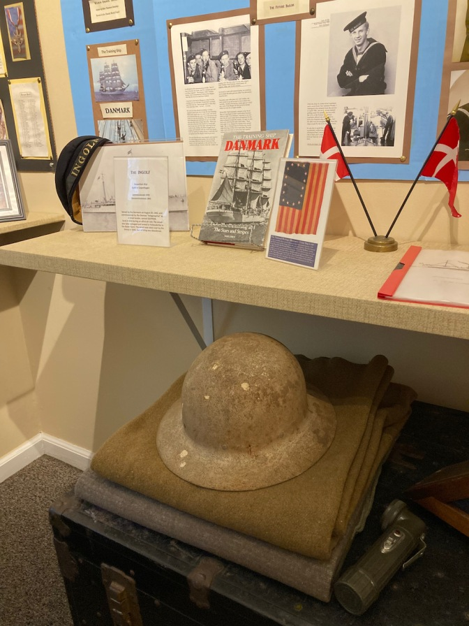 Exhibit on military history, with a WWI helmet, a trunk, and a blanket, as well as photos.