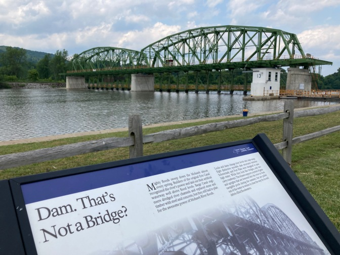 Canal dam, with sign in foreground that says DAM THAT'S NOT A BRIDGE.