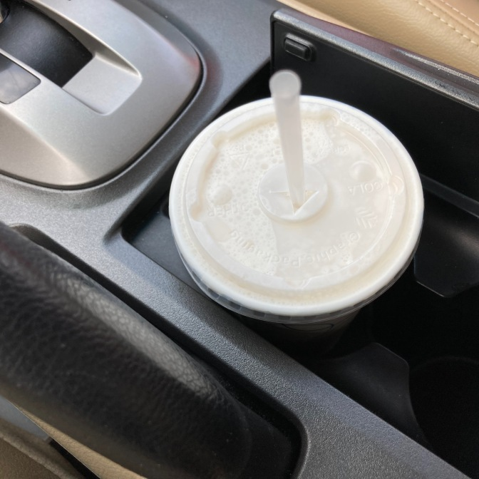 White paper cup with plastic lid in car cupholder.