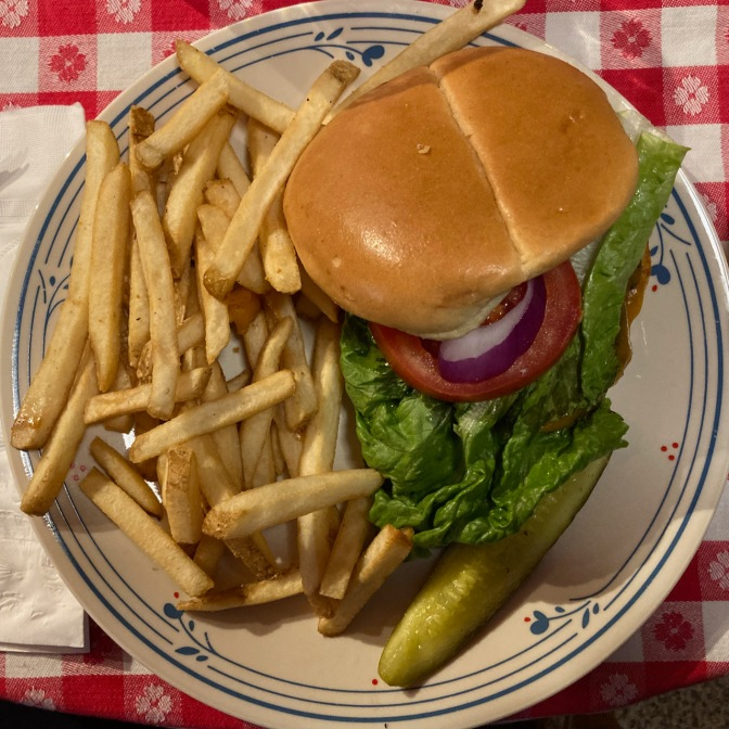 Cheeseburger on plate, with pickle and fries.