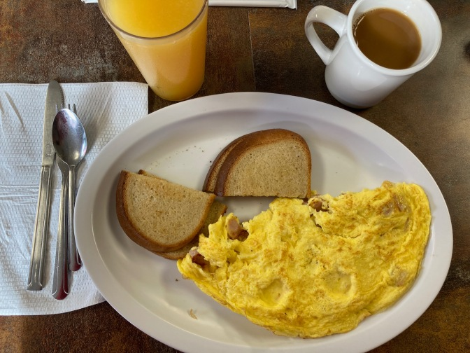 Omelette and toast on plate, with cup of coffee and glass of orange juice on side.