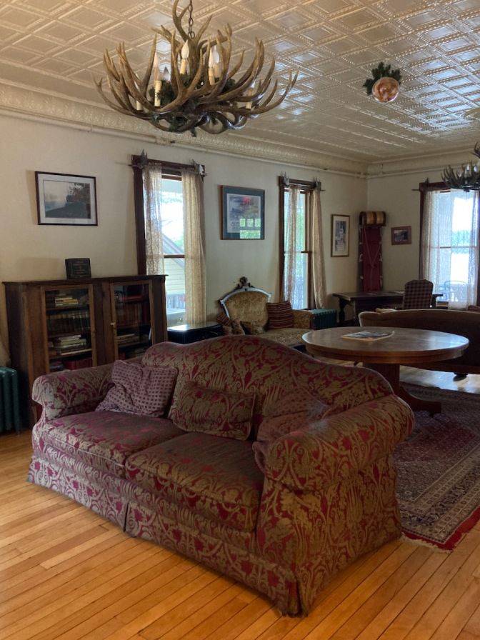 Great Room parlor with sofa in middle of floor, intricate plaster work in ceiling, and deer antler chandelier.