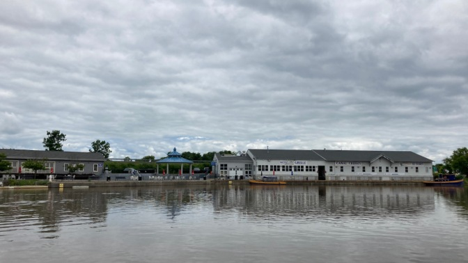 Waterfront of Herkimer along Mohawk River, with pier and buildings for Erie Canal Cruises.
