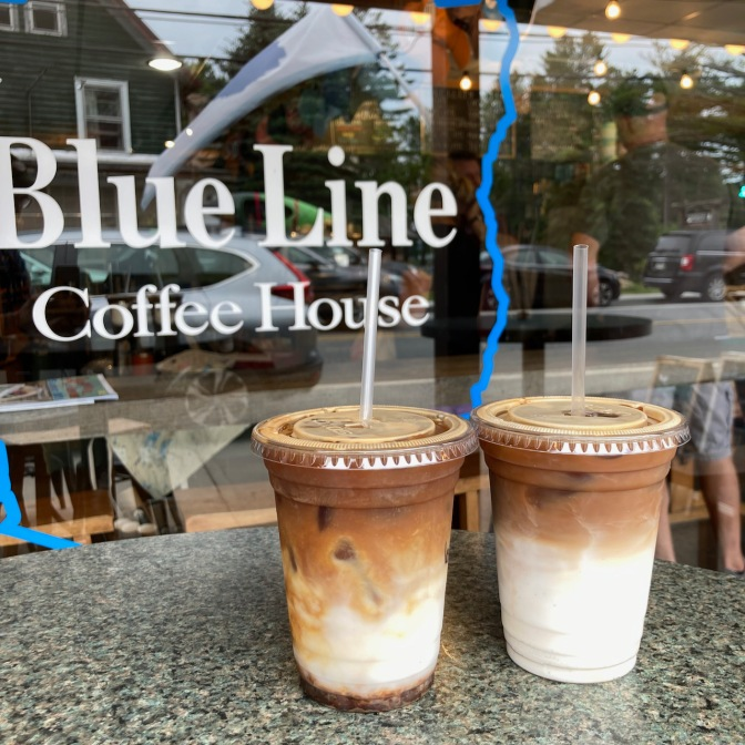 Two lattes on table outside window of Blue Line Coffee House.