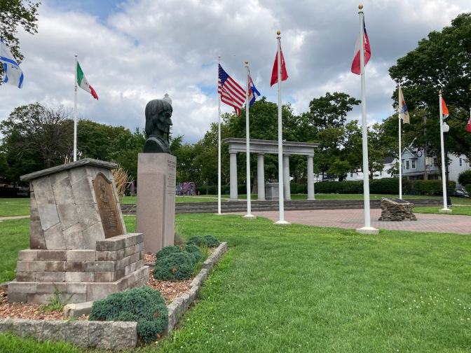Park square, with flags, statues, and monuments.