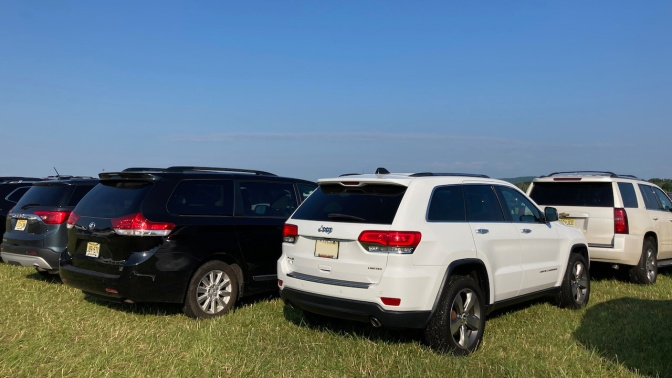 White Jeep Grand Cherokee parked in field.