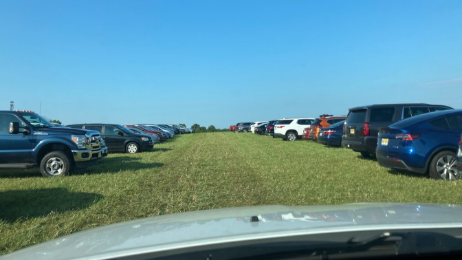 View of grassy field used as parking lot.