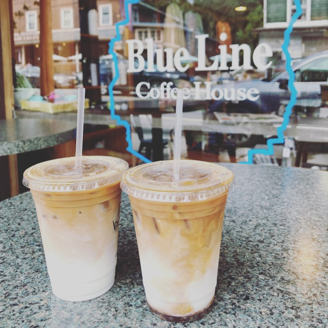 Two lattes on table, with sign on window in background that says BLUE LINE COFFEE HOUSE