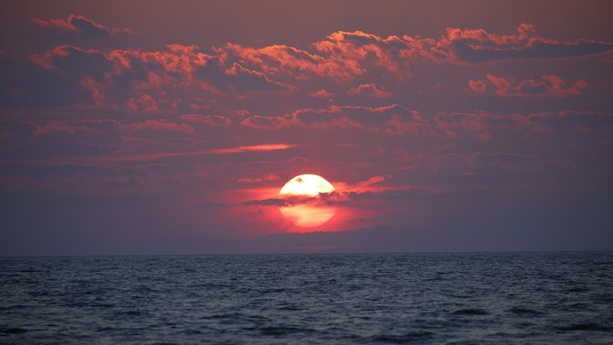 Red sky and sunset over ocean.