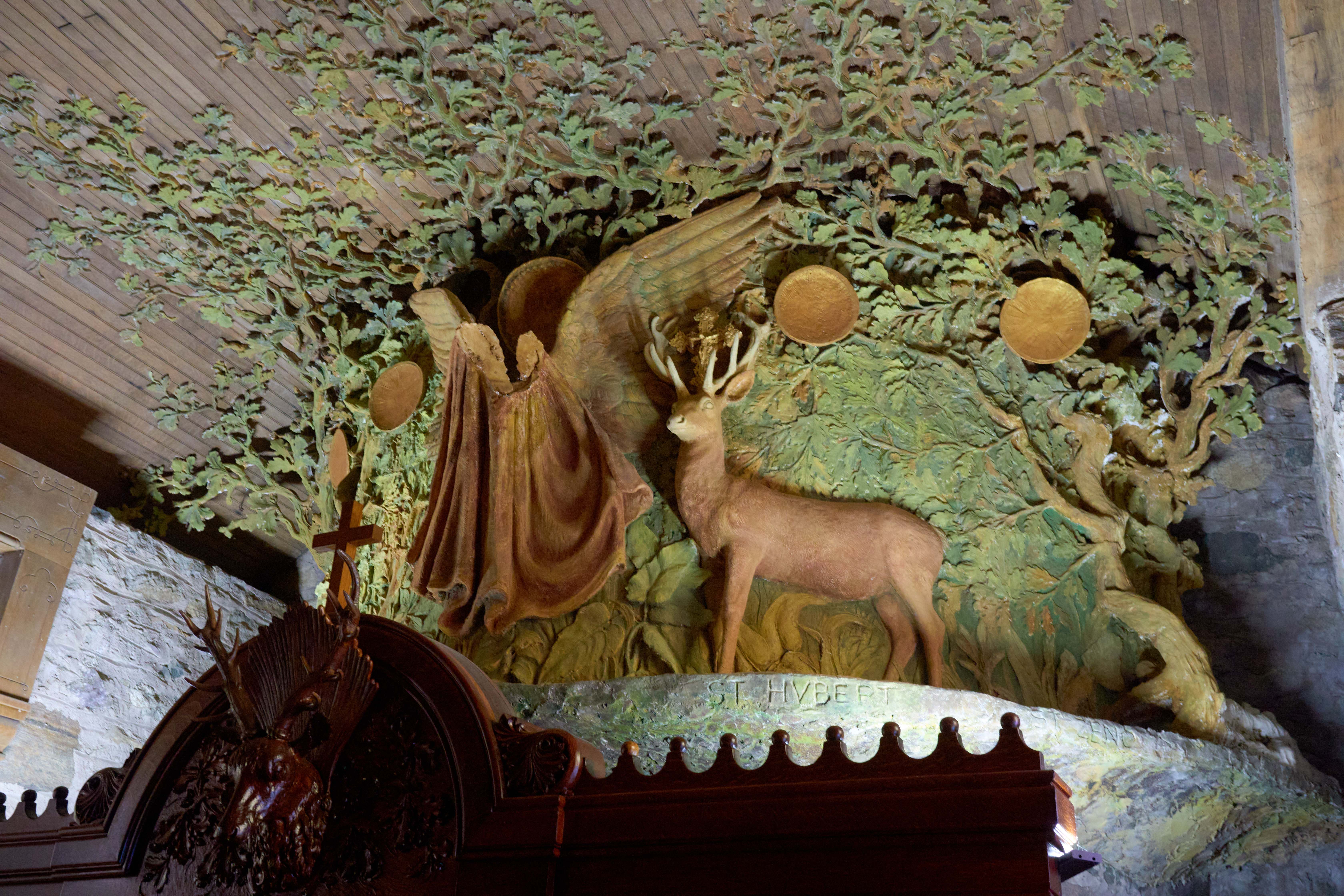 Carved woodland scene on top of confessional.