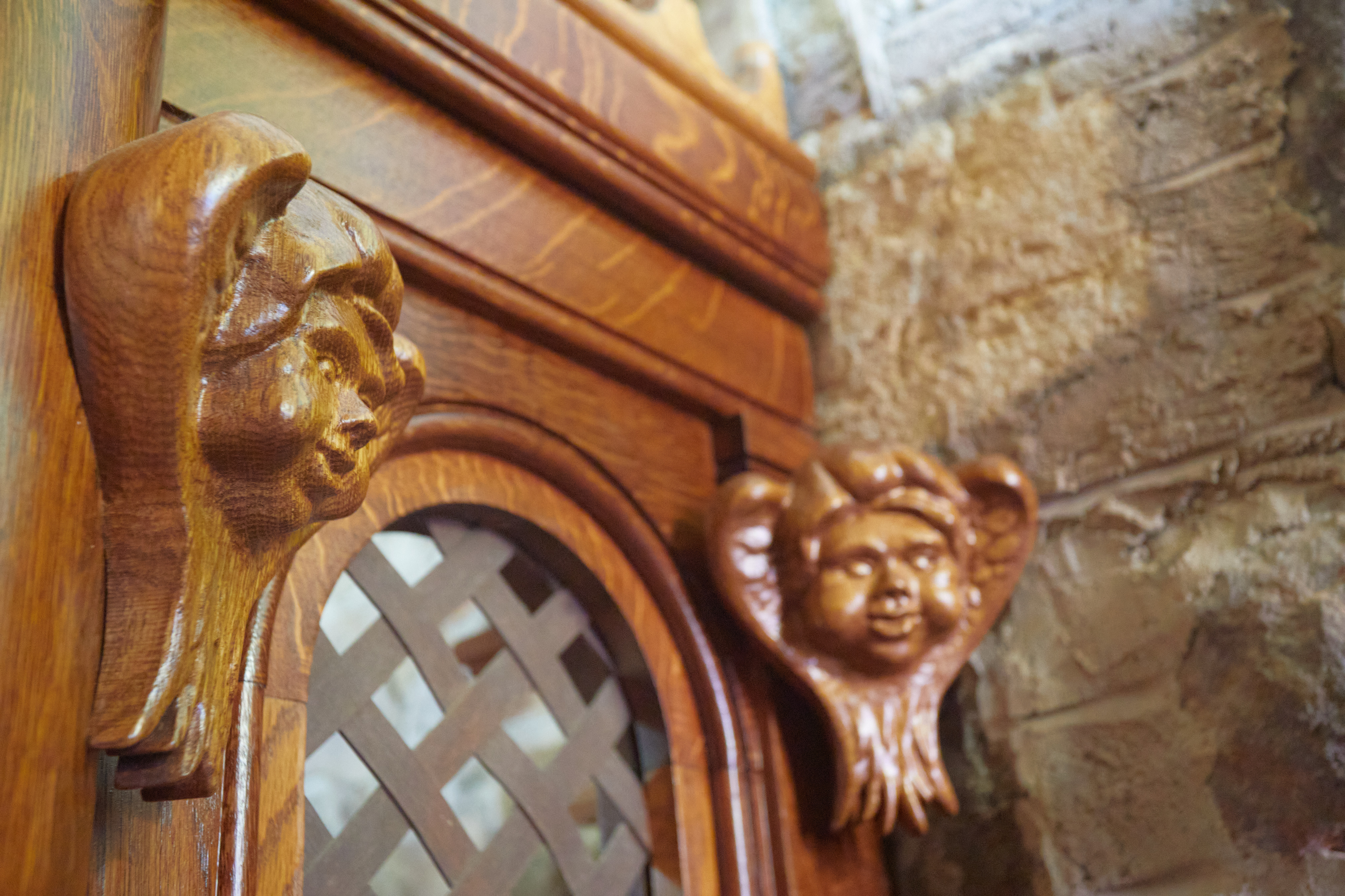 Cherub faces carved into wood on side of confessional.