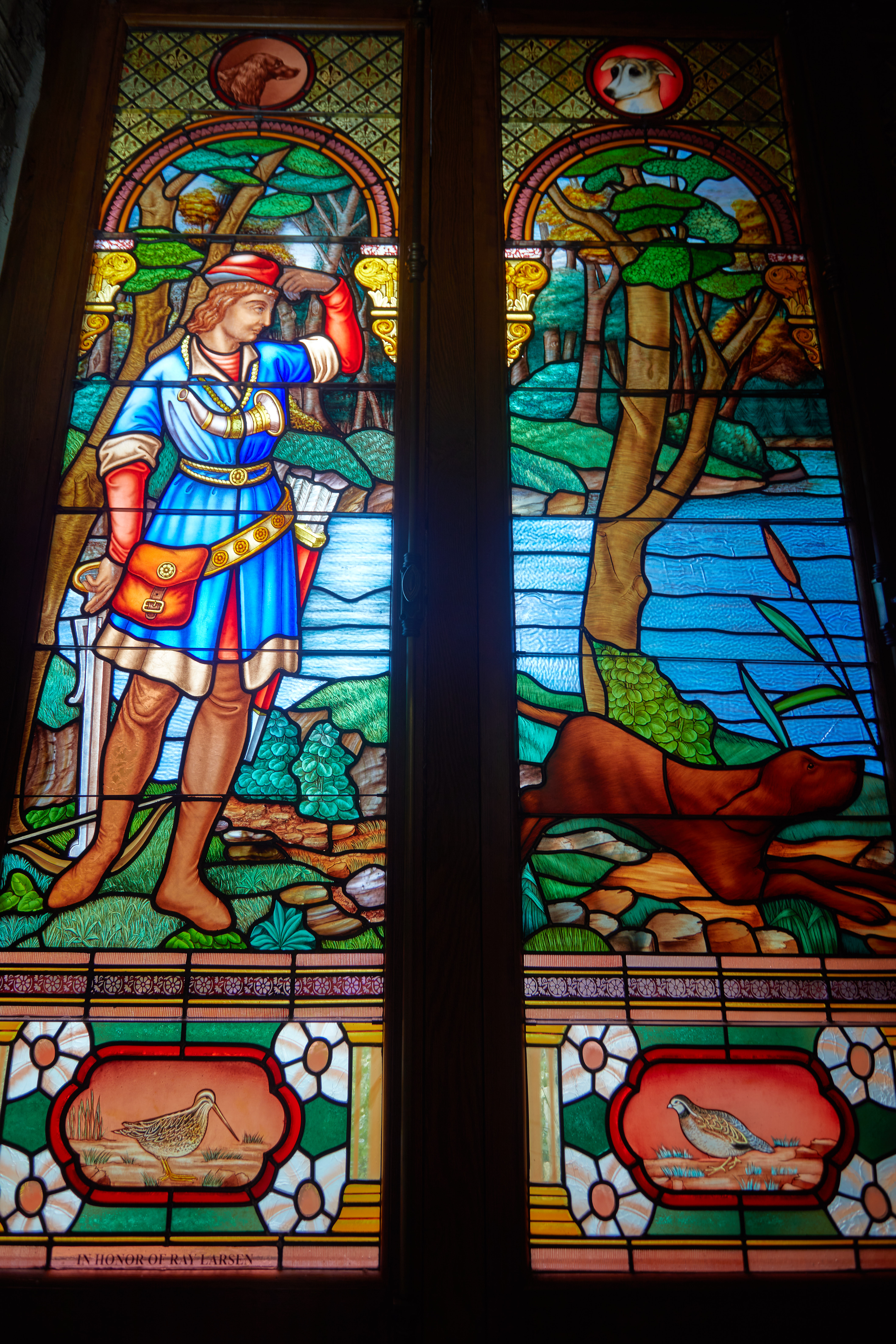 Stained glass window of St. Hubert with a dog.