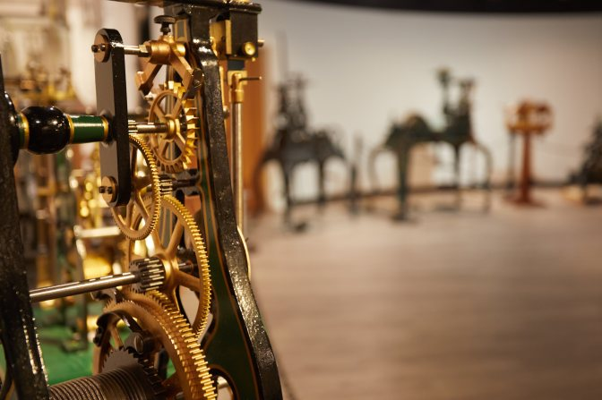 Mechanical interior of clock, with other clocks on display in background.