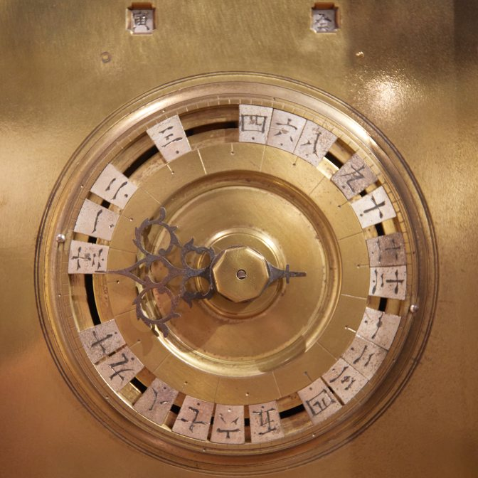 Japanese clock - bronze with writing in Japanese script around clock face.