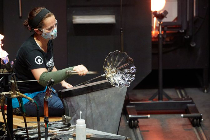 Woman, working with glass bowl on end of blowpipe.