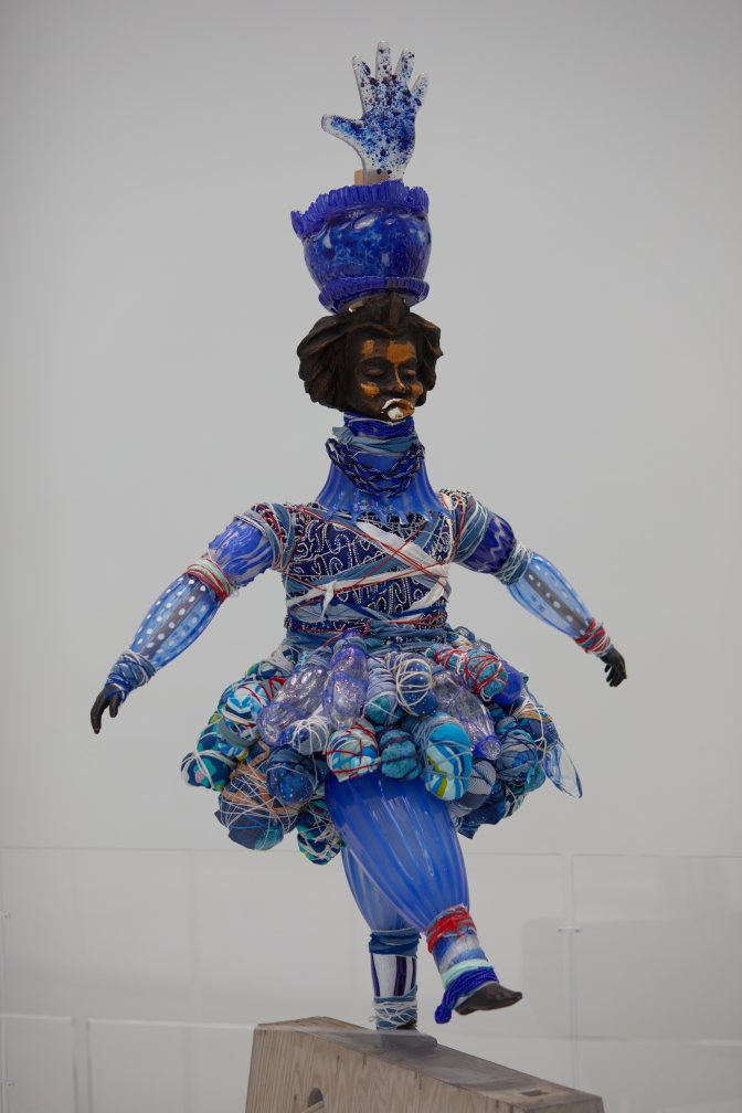 Glass sculpture of man in costume.