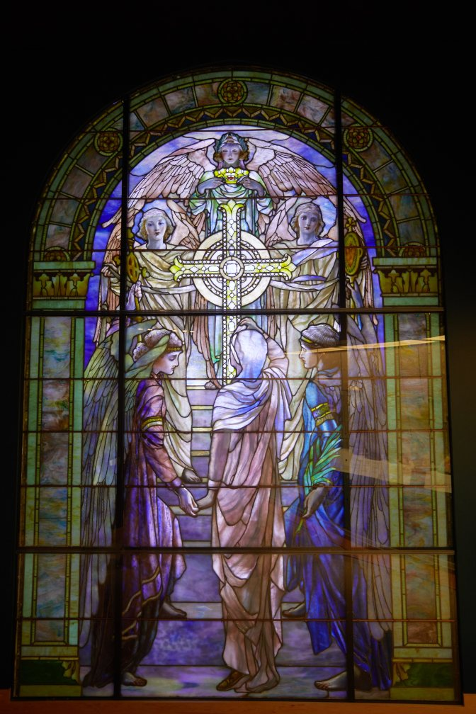 Stained glass window of women and angel surrounding cross.