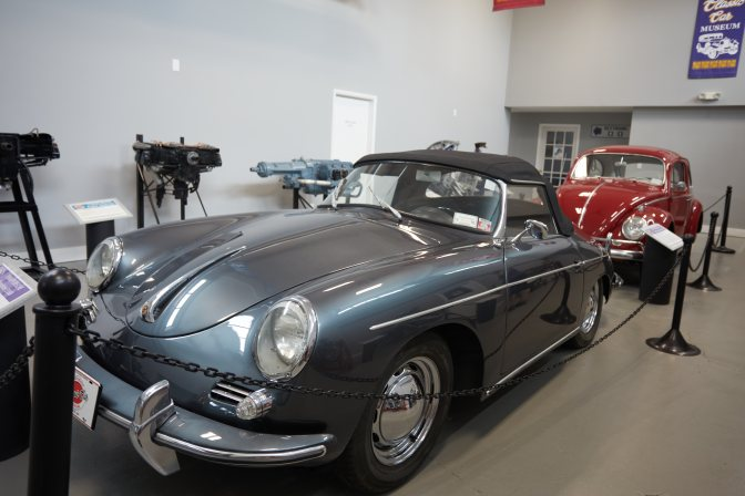 1960 Porsche 356B in gray, with red Beetle behind it.