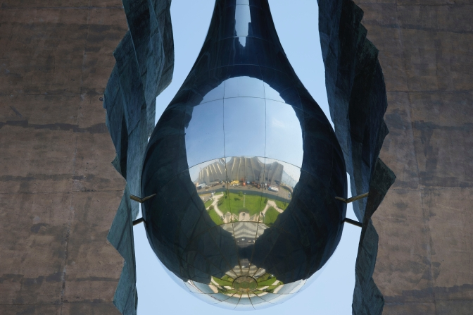 Close-up of metal tear-drop with reflection of surrounding park.