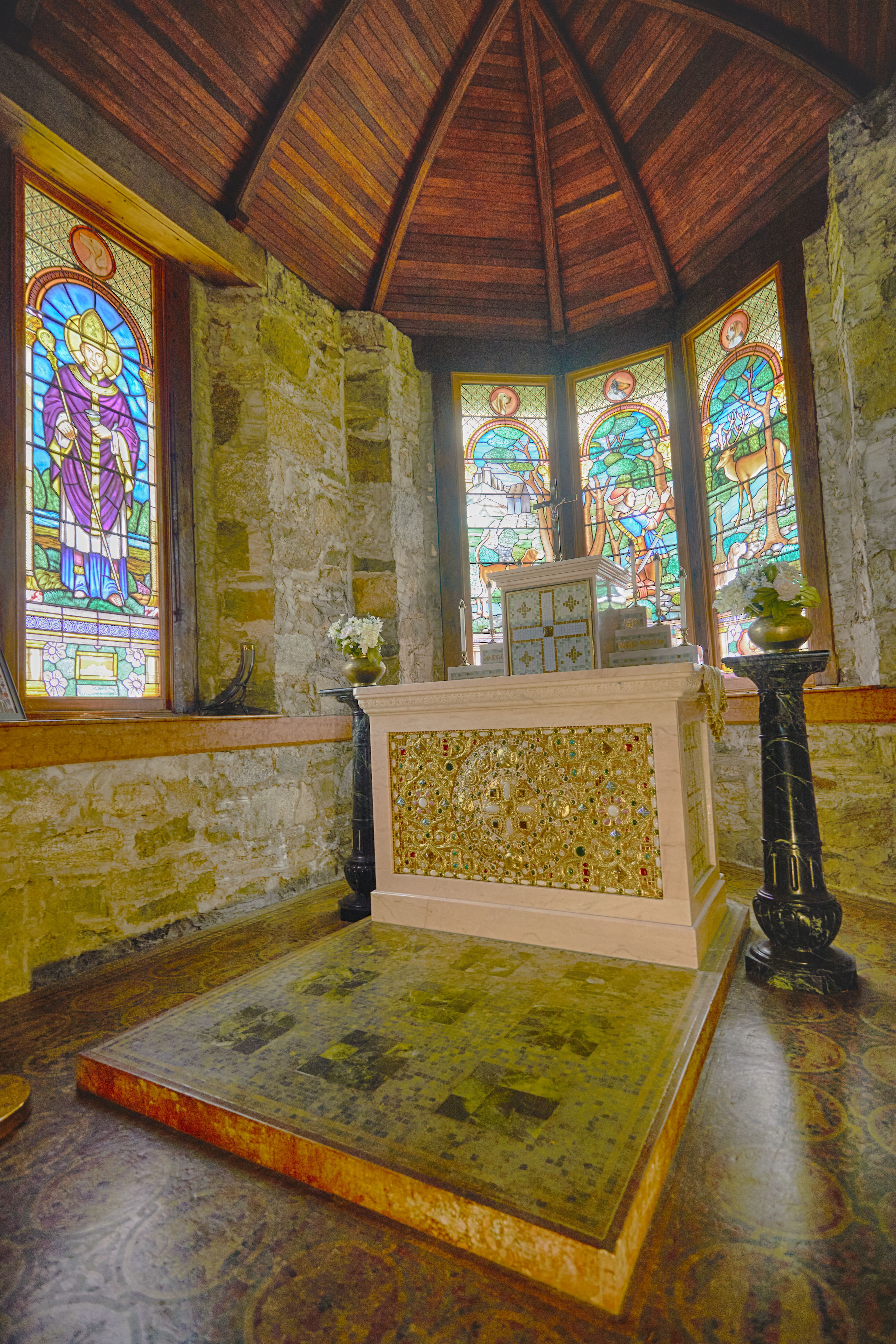 Altar and stained glass windows at front of church.