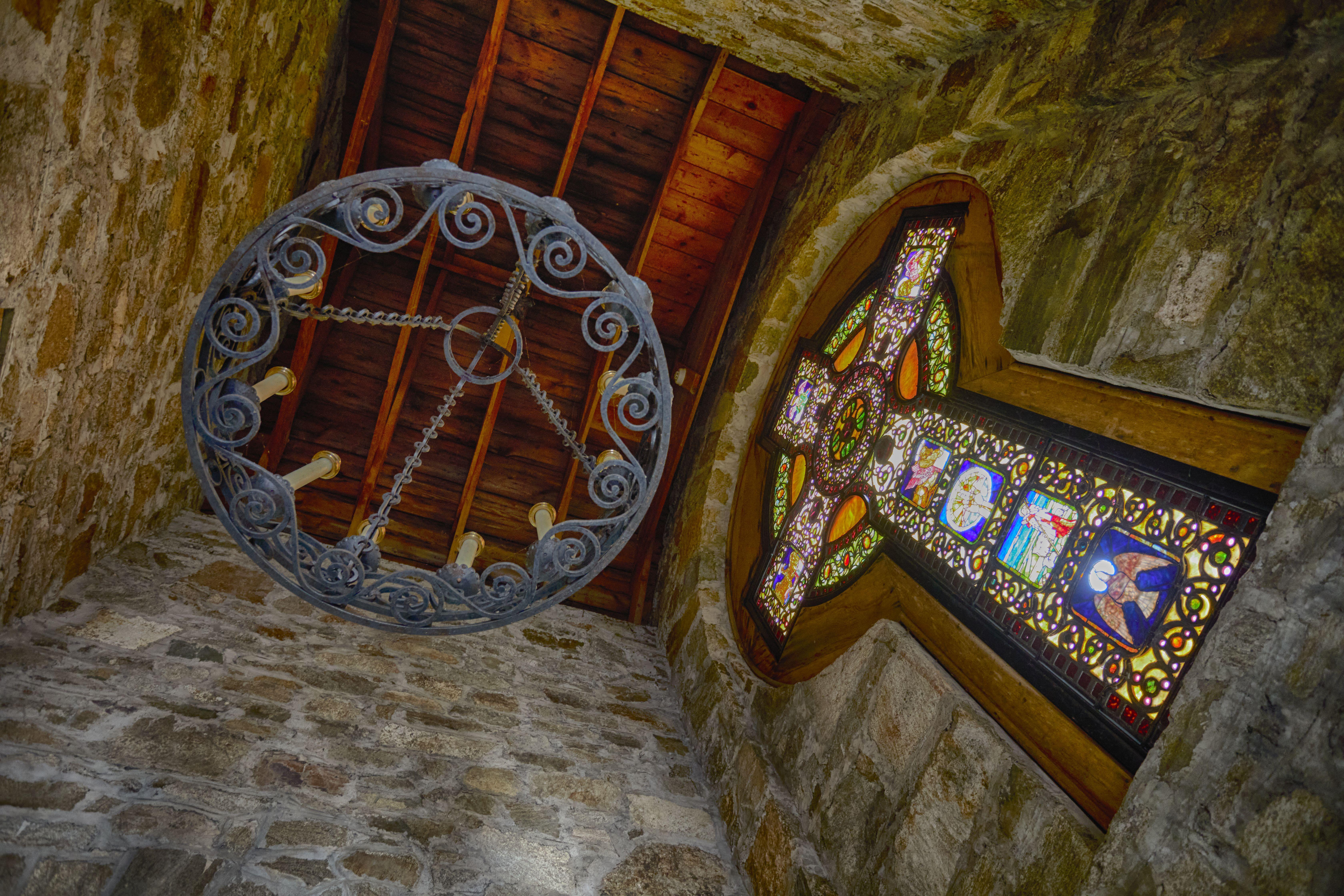 Chandelier hanging from ceiling, beside Celtic Cross. Scene is photographed looking upward.