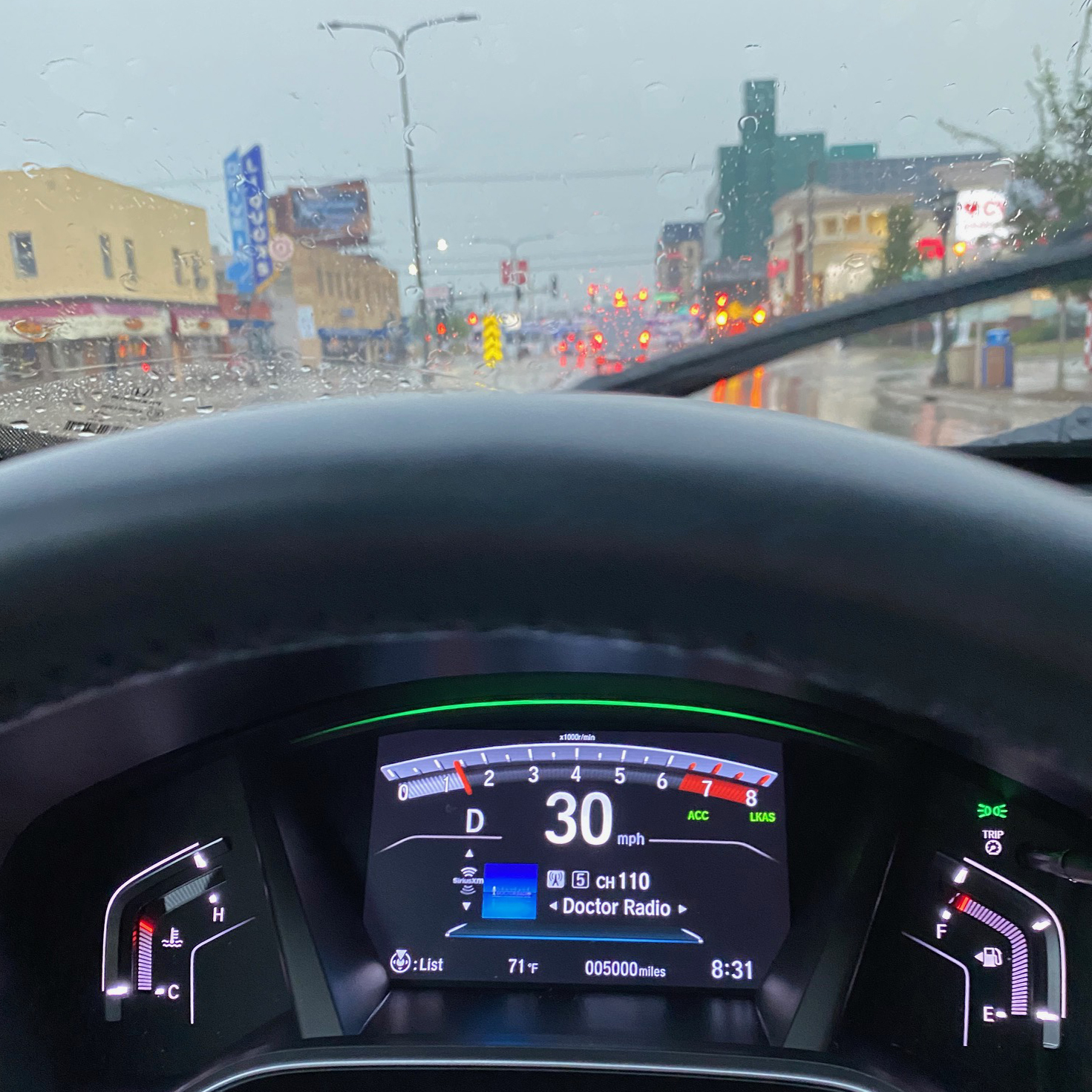 View of rainy street from behind windshield of vehicle. Dashboard in front has odometer that reads 5000 miles.