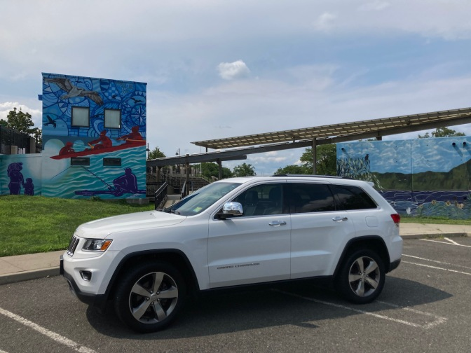 2014 Jeep Grand Cherokee parked in front of building with wall mural.
