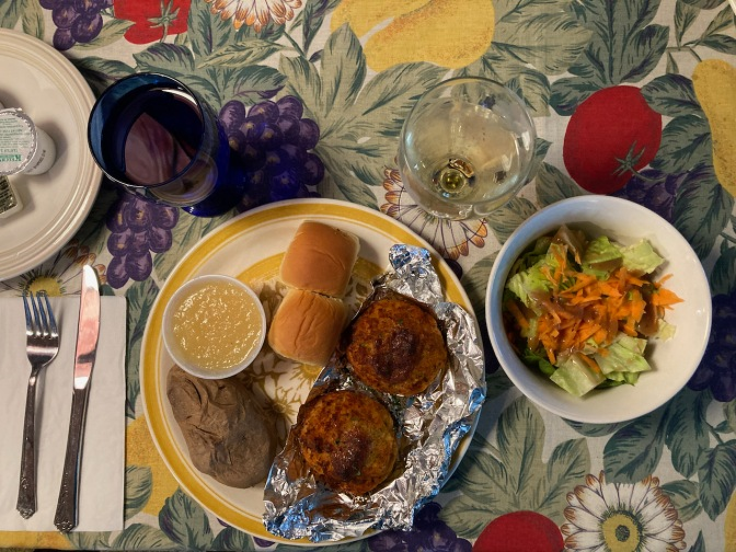 Plate with rolls, baked potato, apple sauce, and crab cakes, with a bowl with salad, a glass of wine, and a glass of water.