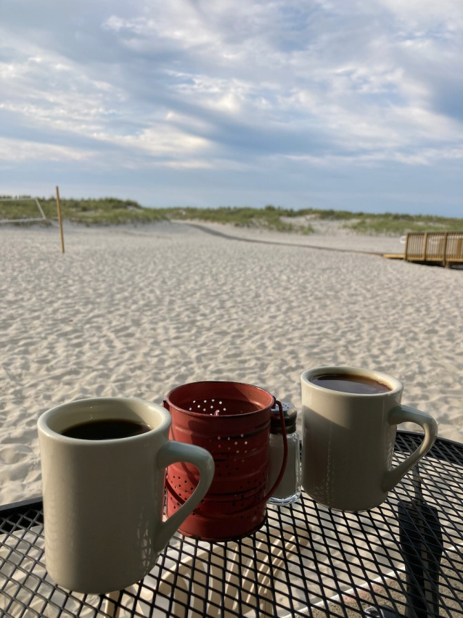 Two cups of coffee on metal table with beach in background.