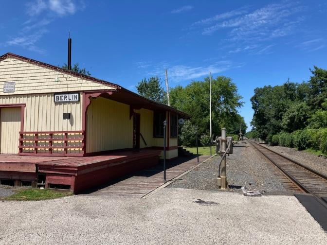Long-A-Coming Depot beside train tracks.