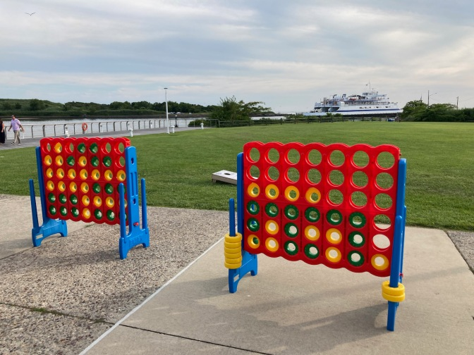 Life-size Connect Four games on patio, with ferry in distance.