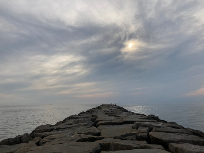 View of jetty extending out into Delaware Bay, with cloudy sky.