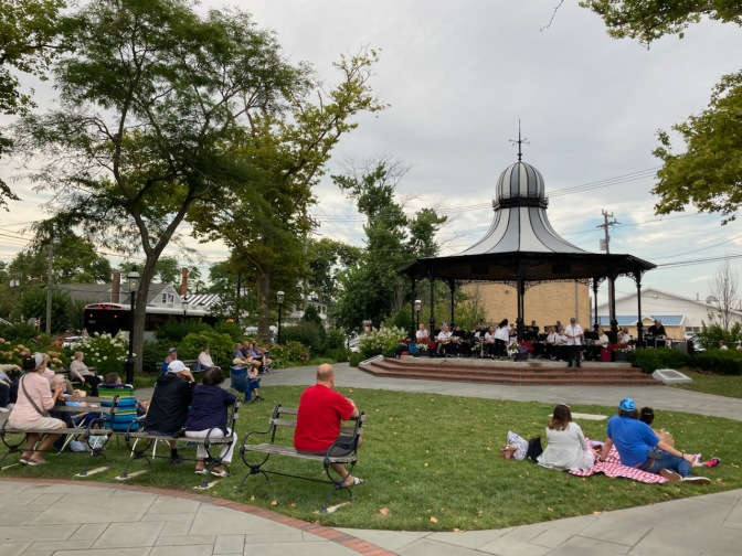 Audience listening to band playing under gazebo in public park.