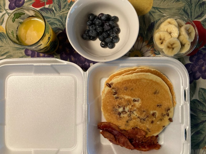Styrofoam container with pancakes and bacon, along with container of bananas, bowl of blueberries, and orange juice.