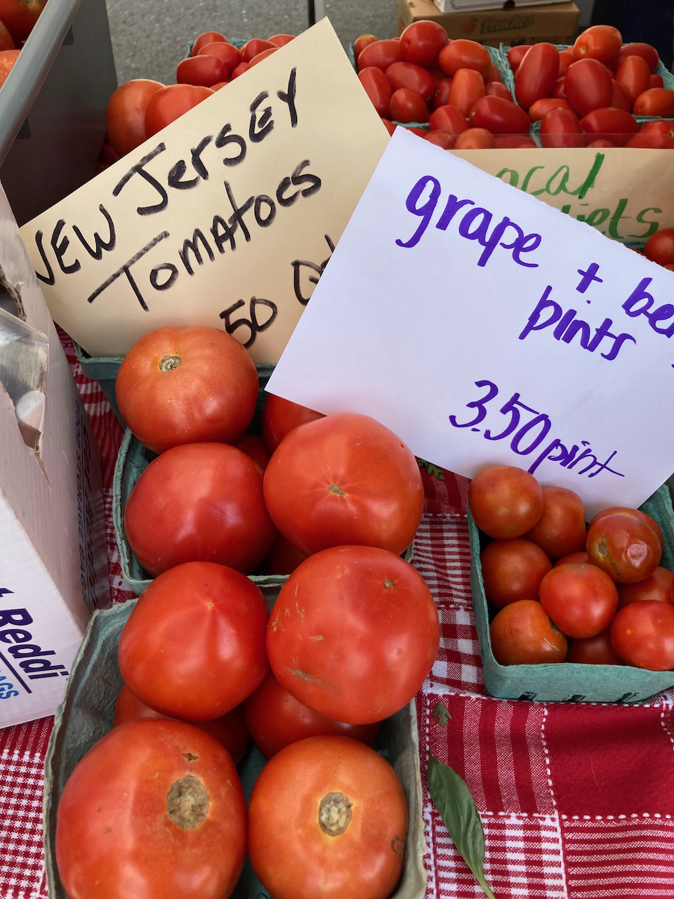 Tomatos on table, with a sign for NEW JERSEY TOMATOES and GRAPE AND BERRY PINTS $3.50 PINT